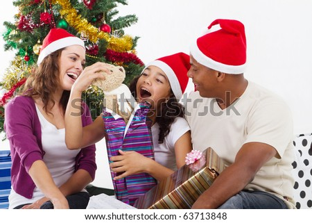 happy family opening Christmas gift at home - stock photo