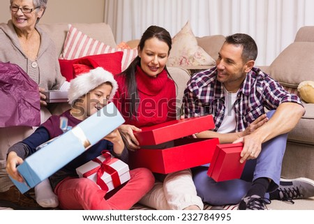 Happy family opening christmas gifts together at home in the living room - stock photo