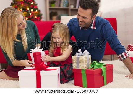 Happy family opening christmas presents  - stock photo