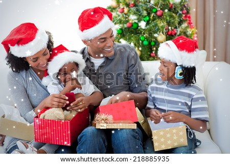 Happy family opening Christmas presents against snow - stock photo
