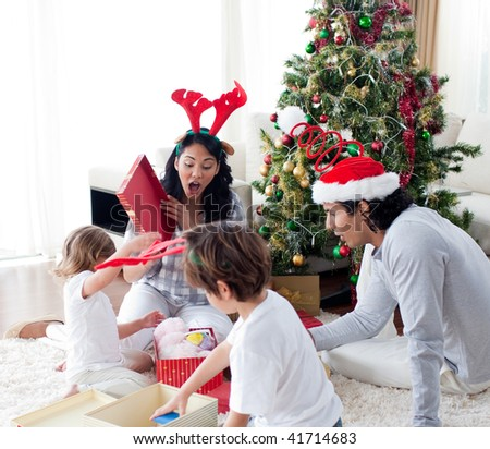 happy family opening Christmas presents at home - stock photo