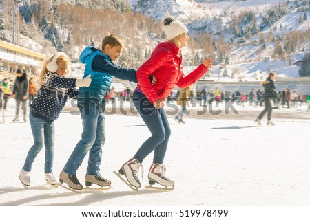 Happy family outdoor ice skating at rink. Winter activities
