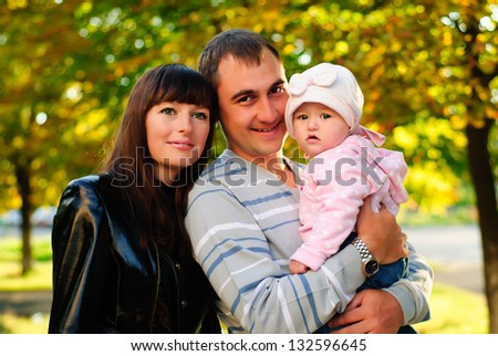 Happy family outdoor - mother, father and daughter are smiling - stock photo