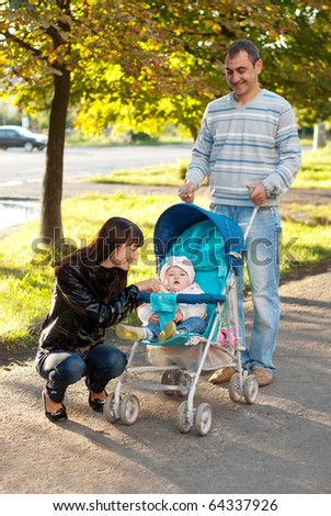 Happy family outdoor - mother, father and dauther are smiling in baby carriage - stock photo