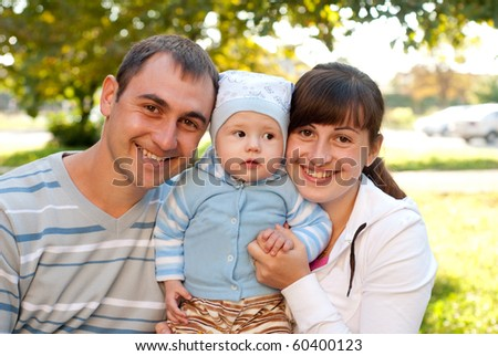 Happy family outdoor - mother, father and son are smiling - stock photo