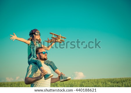 Happy family outdoors. Child playing with father. Dad and son having fun in summer field. Man carrying kid. Child with toy airplane. Kid pretend to be pilot. Travel, vacation and freedom concept - stock photo