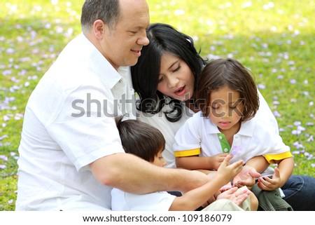 Happy family outdoors in the park having fun - stock photo