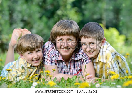 Happy family outdoors on the grass in a park - stock photo