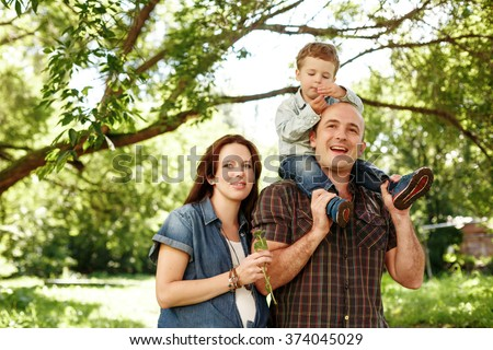 Happy Family Outdoors Walking. Pregnant Woman, Man and Little Boy Sitting on Father. Having Fun. Family Values Concept. Natural Colors. - stock photo