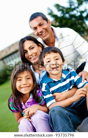 Happy family outdoors with their house behind them - stock photo