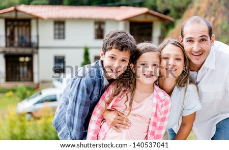 Happy family outside their house in the countryside - stock photo
