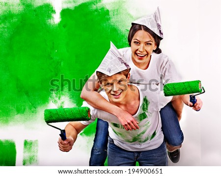 Happy family paint wall at home. - stock photo