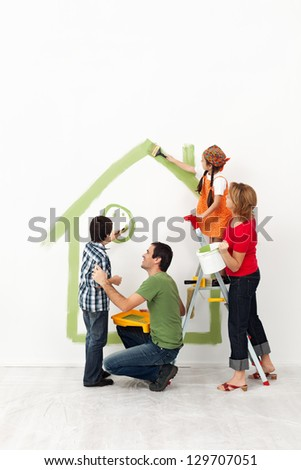 Happy family painting their home together with the kids - stock photo