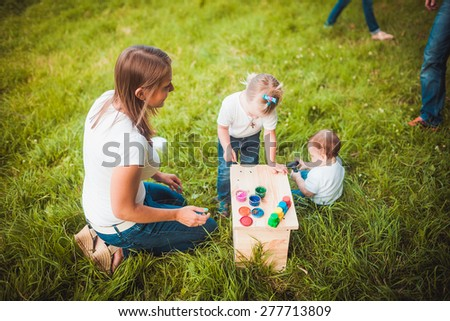Happy family painting wooden parts of birdhouse in garden
