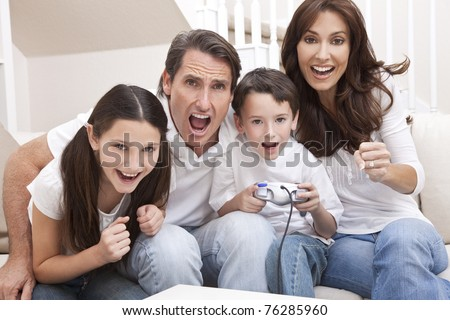 Happy family, parents, son and daughter, having fun playing video console games together, the young boy has the handset controller everyone else is cheering. - stock photo