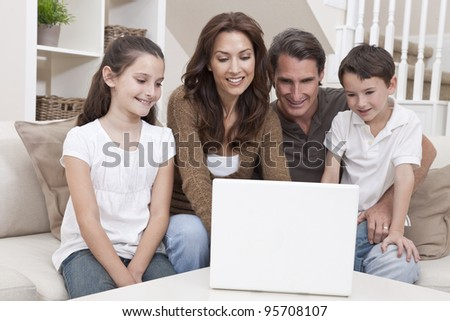 Happy family, parents, son and daughter, having fun using laptop computer together at home on a sofa.