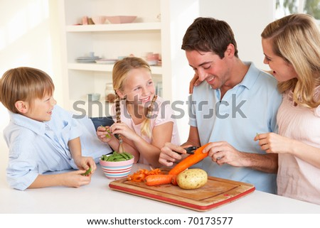Happy family peeling vegetables in kitchen - stock photo