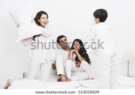 Happy family pillow fight on the bed - stock photo