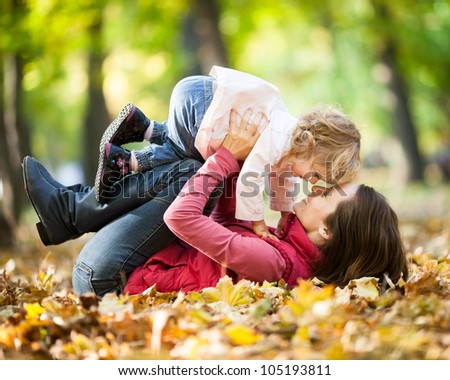 Happy family playing against blurred autumn leaves background - stock photo