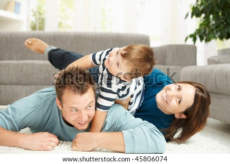 Happy family playing at home, lying heaped on floor in living room.