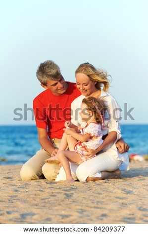 Happy family playing at red sea beach during sunset - stock photo