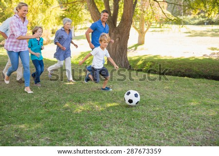 Happy family playing at the ball on a sunny day - stock photo