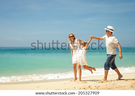 Happy family playing at the beach at the day time. Concept of friendly family. - stock photo