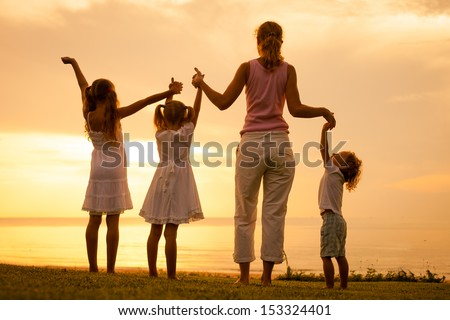 Happy family playing at the beach in the dawn time - stock photo