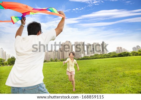 happy family playing colorful kite  in the city park - stock photo