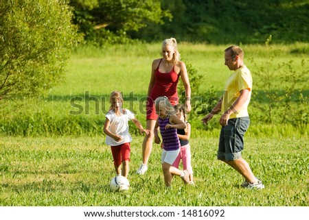Happy family playing football (well, soccer for North America) on a green, sunlit meadow - stock photo