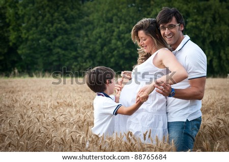 Happy family playing in a wheat field.