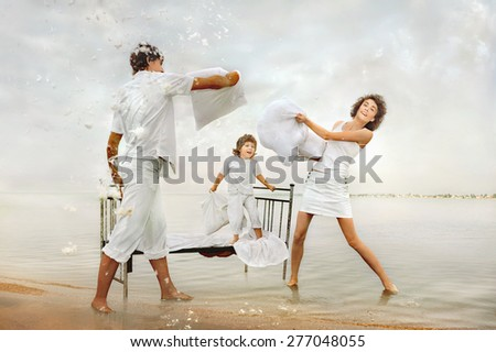 Happy family playing in battle of pillows on sea beach.  - stock photo