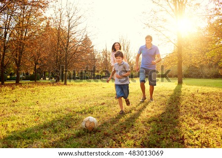 Happy family playing in nature late afternoon sunlight in the fall, summer. Mother, father and son playing with a ball on the grass in the park, laughing and smiling, fun, joy.