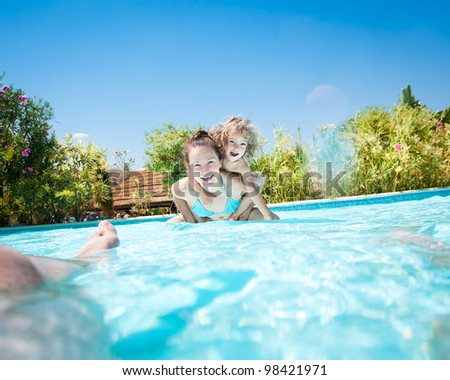 Happy family playing in swimming pool on a tropical resort at the sea. Summer vacations - stock photo