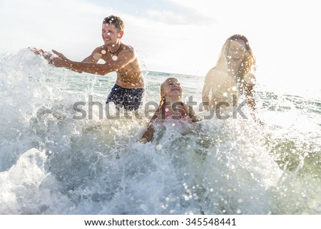 Happy family playing in the ocean and splashing water - Tourists on vacation on a tropical island  - stock photo