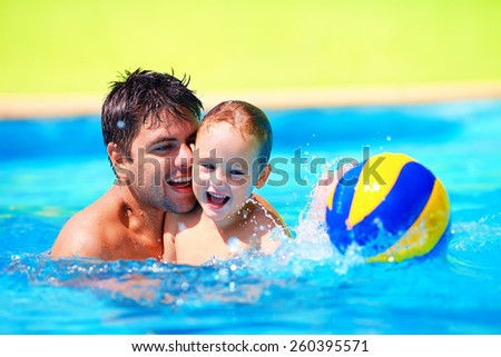 happy family playing in water polo in the pool - stock photo