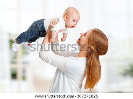 happy family playing mother  throws up child baby at home - stock photo