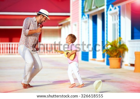 happy family playing music and dancing on caribbean street - stock photo