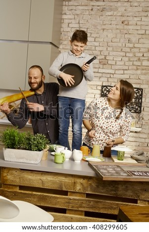 Happy family playing music on kitchen tools, having fun. - stock photo