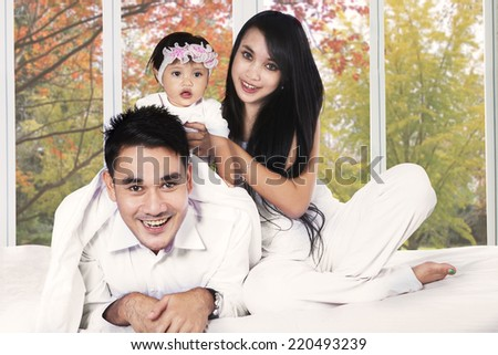 Happy family playing on bedroom with autumn tree background on the window - stock photo