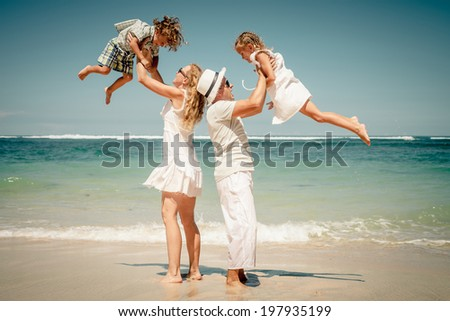 Happy family playing on the beach at the day time - stock photo