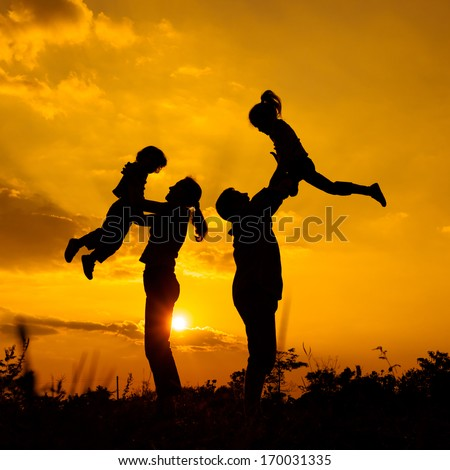 Happy  family playing on the  road in the  sunset time. Evening party on the nature