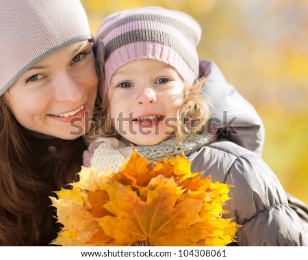 Happy family playing outdoors in autumn park - stock photo