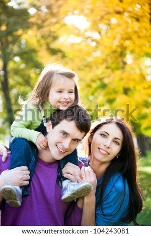 Happy family playing piggyback in autumn park - stock photo