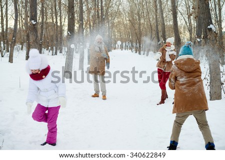 Happy family playing snowballs in winter park - stock photo