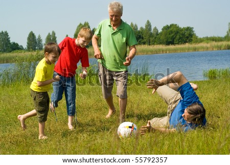happy family playing soccer on the grass - stock photo