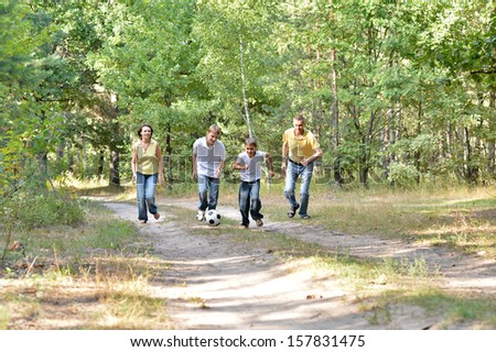 Happy family playing soccer outdoors