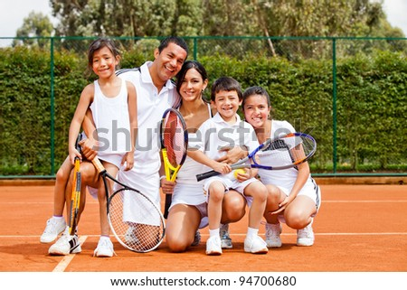 Happy family playing tennis holding rackets and smiling - stock photo