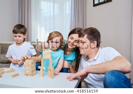 Happy family playing together at home. - stock photo