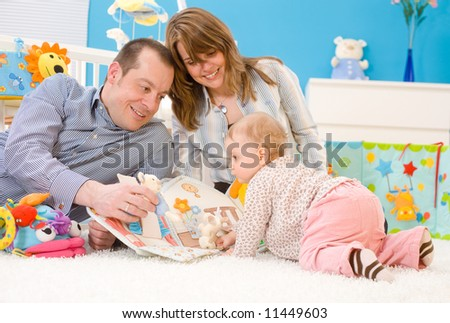 Happy family playing together: mother, father and 1 year old baby girl sitting on floor at children's room, smiling. Toys are officially property released.